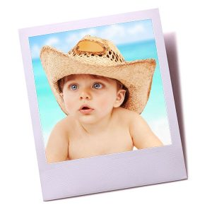 Baby on the beach wearing a straw hat